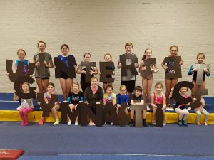 Gymnasts holding letters for new outdoor sign