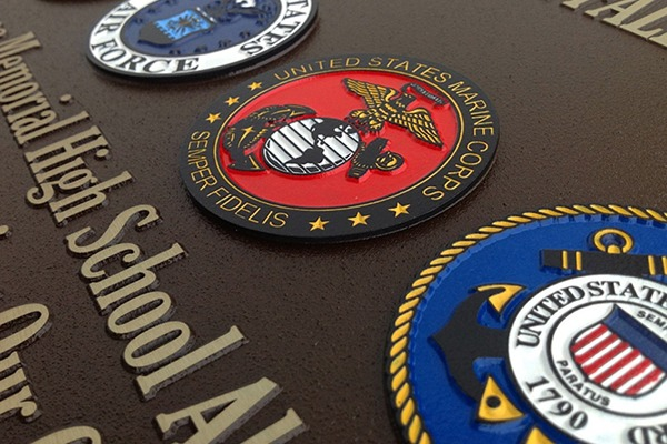 Closeup of color-filled U.S. military seals on magnesium plaque