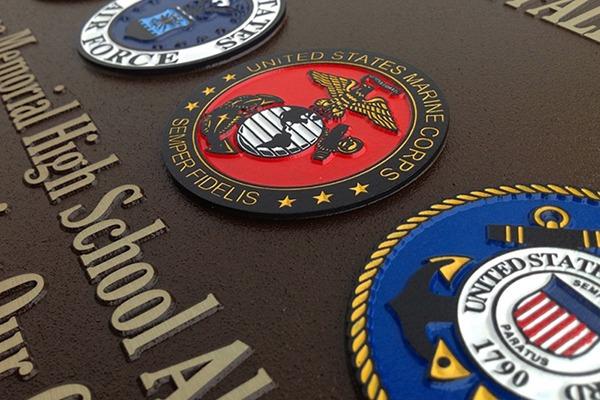 Closeup of color-filled U.S. military seals on magnesium plaque
