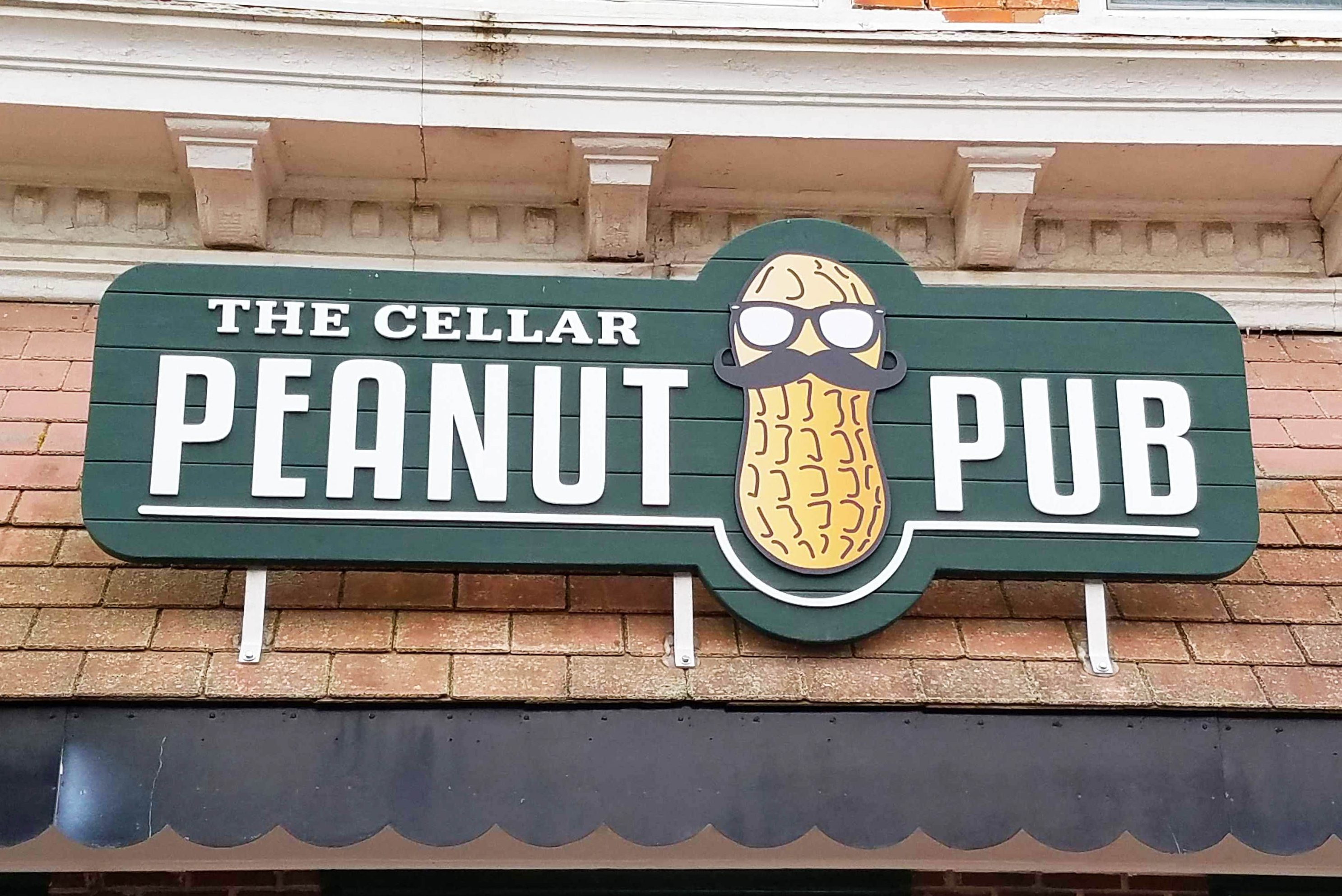 Green storefront sign for The Cellar Peanut Pub featuring peanut logo