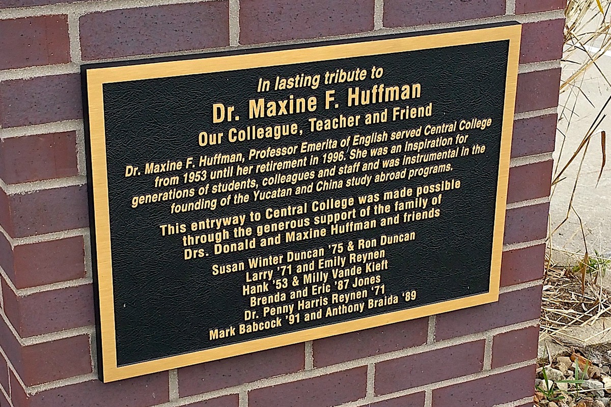 Bronze Central College plaque honoring Dr. Maxine Huffman installed on brick wall