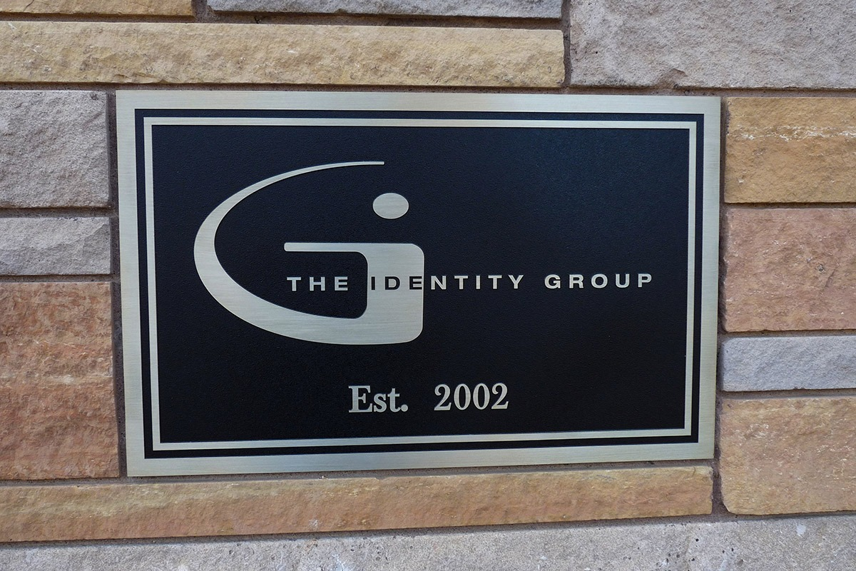 Zinc plaque with Identity Group label installed on brick wall