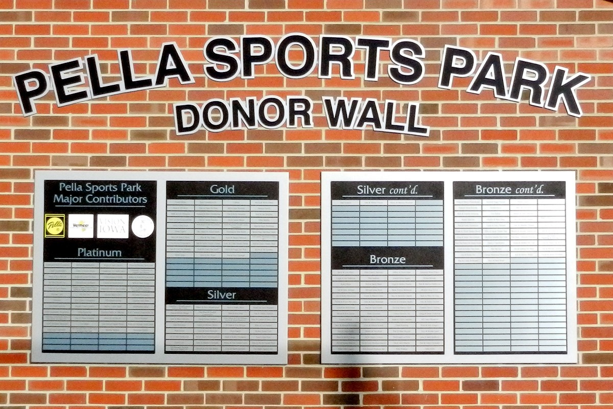 Pella Sports Park donor wall with aluminum cutout letters and Metalphoto plates installed on brick wall