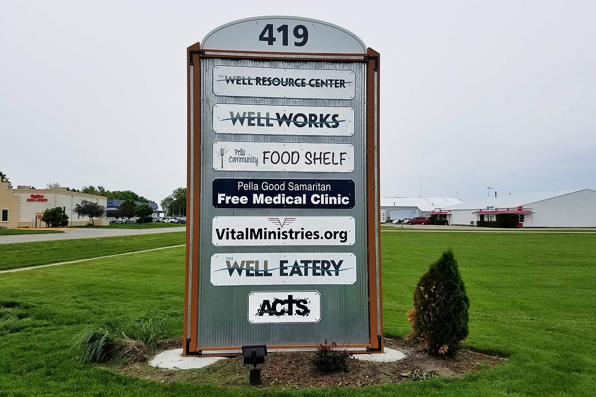 Freestanding aluminum-backed storefront sign for The Well