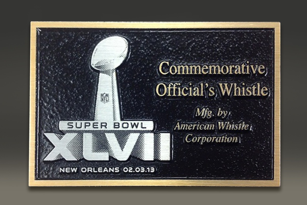 Black magnesium plaque commemorating official's whistle from Super Bowl XLVII