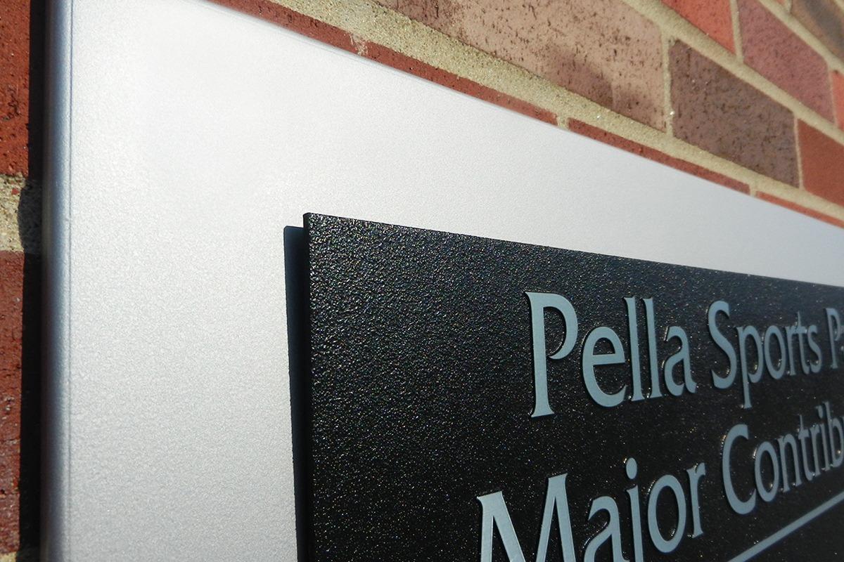 Closeup of black zinc Pella Sports Park donor plaques on aluminum background
