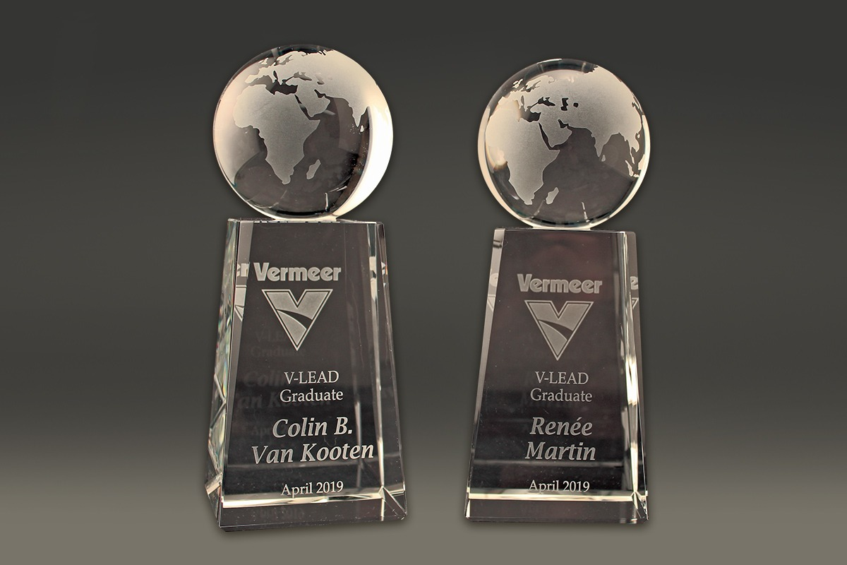 Two sancarved awards with Vermeer logo and cirucluar globes on top