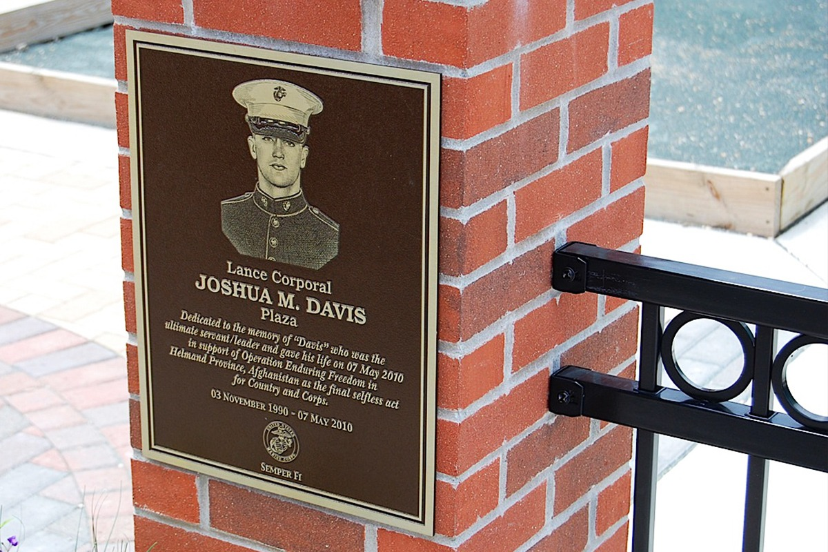 Black and gold Lance Corporal Joshua M. Davis zinc memorial plaque on brick wall