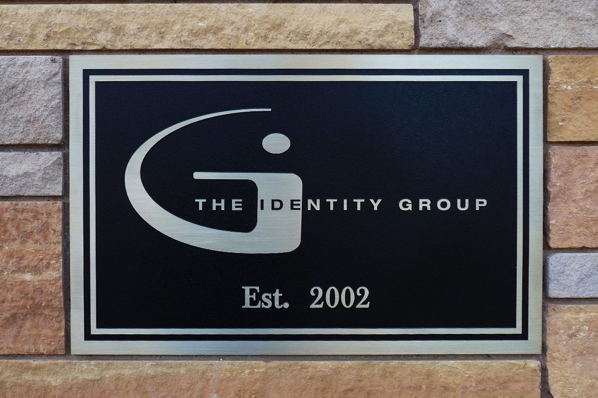 Black and gold zinc plaque with Identity Group logo on brick wall