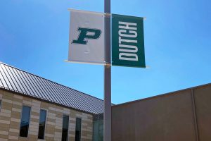 Two Pella Dutch banners on lampposts in school parking lot