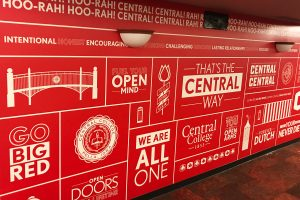 Stickers with inspirational sayings on red wall in college cafe