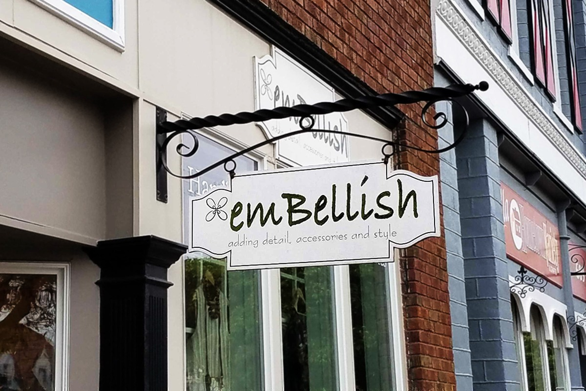Hanging storefront sign with script font for Embellish boutique in Pella Iowa