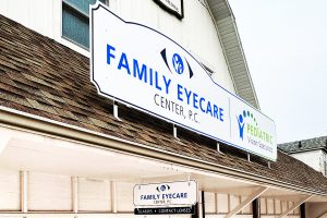 Eyecare business sign with blue vinyl letters mounted on roof