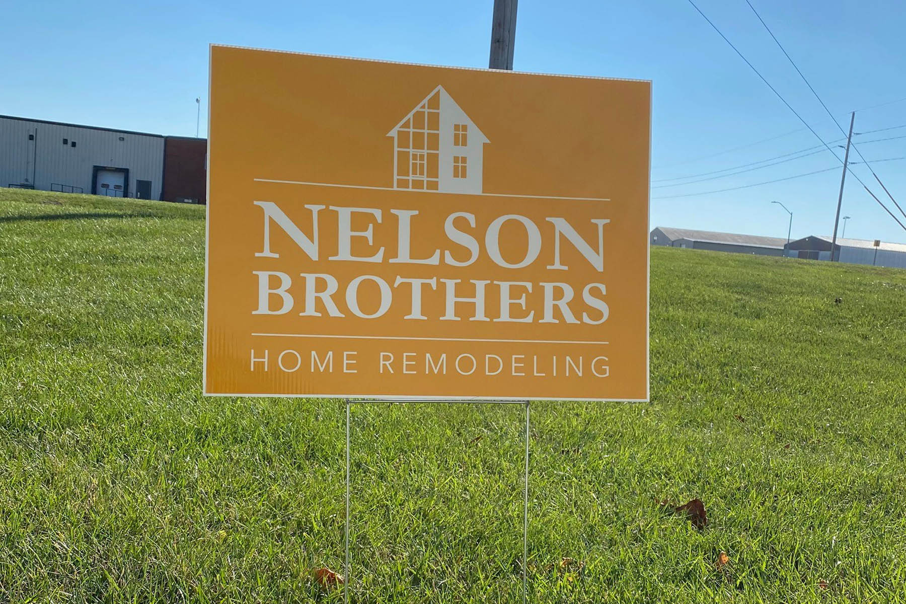 Yellow Nelson Brothers Home Remodeling yard sign featuring illustration of house