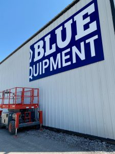 Closeup of Blue Equipment sign being installed