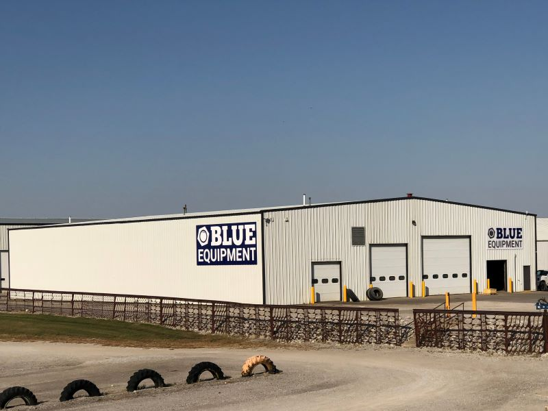 Wide view of Blue Equipment sign on white Kinze Manufacturing building